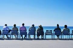 Leute, die das Meer bei Promenade des Anglais in Ni gegenüberstellend sitzen Lizenzfreie Stockfotografie