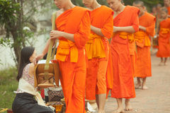 Leute, die den buddhistischen Mönchen auf der Straße, Luang Prabang Almosen, am 20. Juni 2014 geben Stockbilder