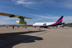 Leute, die den Flugzeuge Sukhoi-SuperJet 100-95 betrachten Stockfotografie