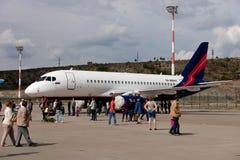 Leute, die den Flugzeuge Sukhoi-SuperJet 100-95 betrachten Stockbilder