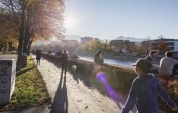 Leute, die den Flussufer genießen Lizenzfreie Stockbilder