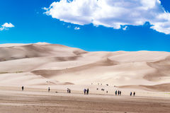 Leute, die in den Sanddünen wandern Lizenzfreies Stockbild