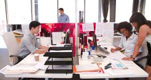 Leute, die an den Schreibtischen im modernen Bürogroßraum arbeiten