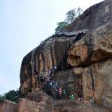 Leute, die den Sigiriya-Felsen Sri Lanka klettern Stockfotografie