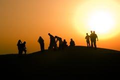 Leute, die den Sonnenuntergang in der Sahara-Wüste aufpassen Lizenzfreie Stockfotografie