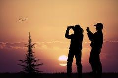 Leute, die den Sonnenuntergang mit ihrem Handy fotografieren Lizenzfreie Stockfotos