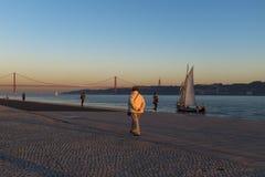 Leute, die den Sonnenuntergang nahe dem Tajo mit den 25 von April Bridge Ponte 25 de Abril auf dem Hintergrund, in der Stadt von  Lizenzfreies Stockbild
