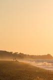 Leute, die den Strand und den Sonnenuntergang gehen und genießen Lizenzfreie Stockbilder
