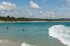 Leute, die in den Strand von Byron Bay surfen Stockfotos