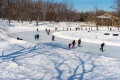 Leute, die an der natürlichen Eisbahn Lafontaine-Parks eislaufen Stockbilder