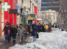 Leute, die in die Mitte von Bukarest-Stadt, Rumänien gehen Kleines Haus im Schnee deckte Holz in den Schweizer Alpen ab Lizenzfreies Stockbild