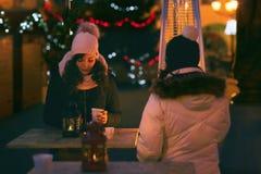 Leute, die draußen an Weihnachtsdurchschlag auf Weihnachtsabend nippen Stockfotos