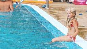 Leute, die durch den Poolside eines ErholungsortSwimmingpools sitzen stock video footage