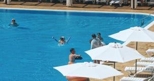 Leute, die durch den Poolside eines ErholungsortSwimmingpools während der Sommerferien sitzen stock video footage