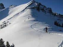 Leute, die durch Schnee zur Gebirgsspitze wandern Stockbild