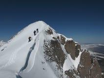 Leute, die durch Schnee zur Gebirgsspitze wandern Lizenzfreie Stockfotografie