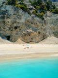 Leute, die an Egremni-Strand, Lefkas, Griechenland suntanning sind lizenzfreie stockbilder