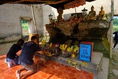 Leute, die Ehrerbietung zu allgemeiner alter thailändischer Buddha-Statue beten, die im Tempel für hundert Jahre gelassen wird Stockfoto