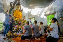 Leute, die Ehrerbietung zu allgemeiner alter thailändischer Buddha-Statue beten, die im Tempel für hundert Jahre gelassen wird Lizenzfreies Stockfoto