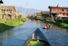 Leute, die ein Boot am Dorf von Maing Thauk auf See Inle rudern Lizenzfreies Stockfoto