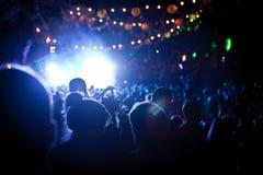 Leute, die ein Festivalstadium nachts mit Farbbeleuchtung betrachten Stockfotos