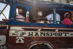Leute, die in ein local bus des alten Busses in Senegal reisen Lizenzfreies Stockfoto
