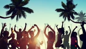 Leute, die eine Partei durch den Strand haben Stockfotos