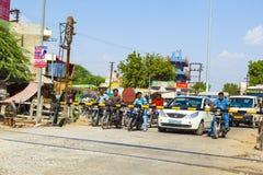 Leute, die an einem Bahnübergang nahe Jaipur, Indien warten Lizenzfreie Stockbilder