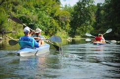 Leute, die in einem kleinen Fluss im Sommer canoeing sind stockbilder