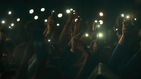 Leute, die an einem Konzert in einem Nachtklub tanzen und ein Taschenlampentelefon in ihren Händen wellenartig bewegen stock video
