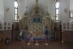 Leute, die in einem Tempel zu Ehren der Ikone Mutter des Gottes Semistrelnaya im Dreiheits-Georgievskyfraukloster beten Stockfoto