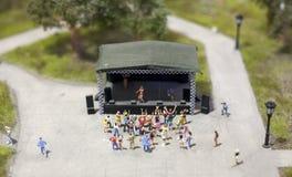 Leute, die in einen Park an einem Konzert vor dem Stadium in einer Miniaturwelteinrichtung tanzen lizenzfreie stockfotografie