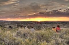 Leute, die einen Sonnenuntergang auf einem Hügel aufpassen Stockbild