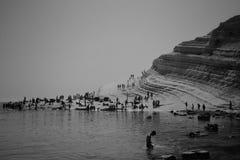 Leute, die einen Tag an einem Strand nahe einem Felshügel genießen lizenzfreies stockfoto