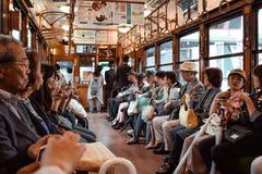 Leute, die in einer historischen Straßenbahn zu Arashiyama in Kyoto sitzen lizenzfreie stockbilder