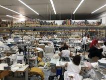 Leute, die in einer nähenden Abteilung der Textilfabrik arbeiten stockfotos