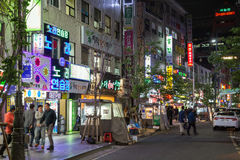 Leute, die an einer Straße in Seoul nachts gehen stockfotografie