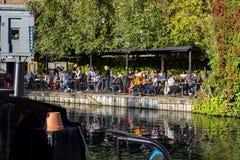 Leute, die an einer Taverne auf den Kanalufern am Kanal des Regenten nahe bei Paddington in kleinem zu Mittag essen lizenzfreie stockfotos