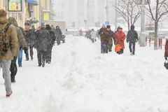 Leute, die entlang Bürgersteig unter großen Schneestapel gehen Typischer Winter stockfotos