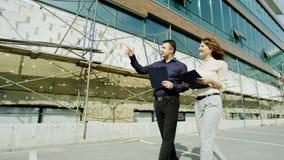Leute, die entlang das Gebäude gehen Lizenzfreies Stockbild