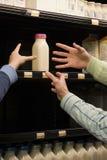 Leute, die für Milch erreichen stockbilder