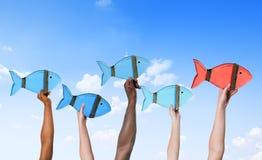 Leute, die Fisch-Symbole und Führungs-Konzept halten Lizenzfreie Stockfotos