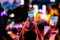 Leute, die Fotos von Mengen mit Handy machen stockbild