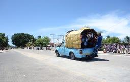 Leute, die gefährlich mit überfülltem Packwagen reisen Lizenzfreies Stockfoto