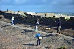 Leute, die gegen sehr starken Wind auf einer herausgestellten Stelle auf den Klippen von Moher in Irland kämpfen lizenzfreies stockbild