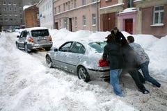 Leute, die gehaftetes Auto in der schneebedeckten Straße drücken Stockfotografie