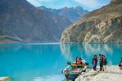 Leute, die gehen, ein Boot am Attabad See, mit Blick auf Gebirgshintergrund zu mieten stockfotografie