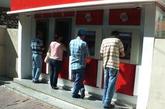 Leute, die Geld von ATM-Maschinen zurücknehmen Stockfotos