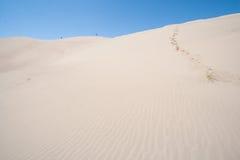 Leute, die am großen Sanddüne-Nationalpark in Colorado gehen Stockfotografie
