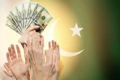 Leute, die Hände mit Dollar und Flagge Pakistan auf Hintergrund hissen Patriotisches Konzept lizenzfreie stockfotografie